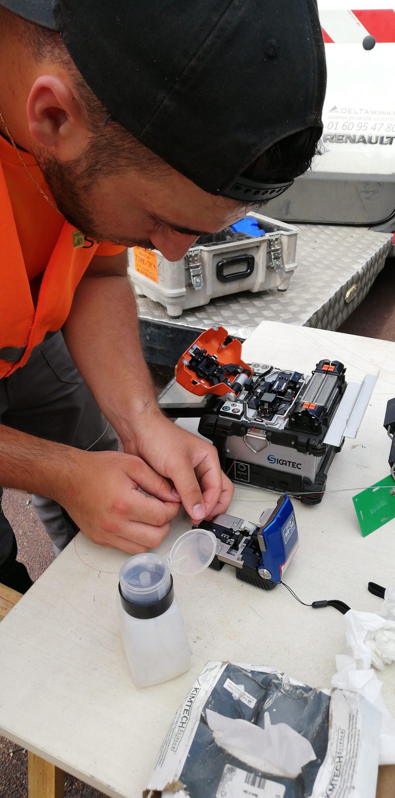 Un stagiaire s'initie à la soudure optique sur un chantier